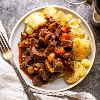 venison bourguignon on a plate with smashed potatoes. Wine in the background.