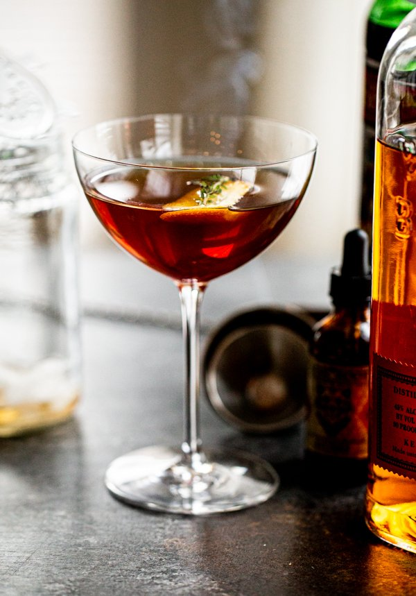 a smoked manhattan cocktail on a grey counter