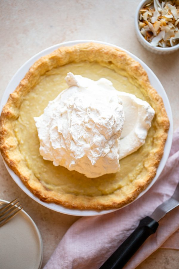 whipped cream mounded on coconut cream pie