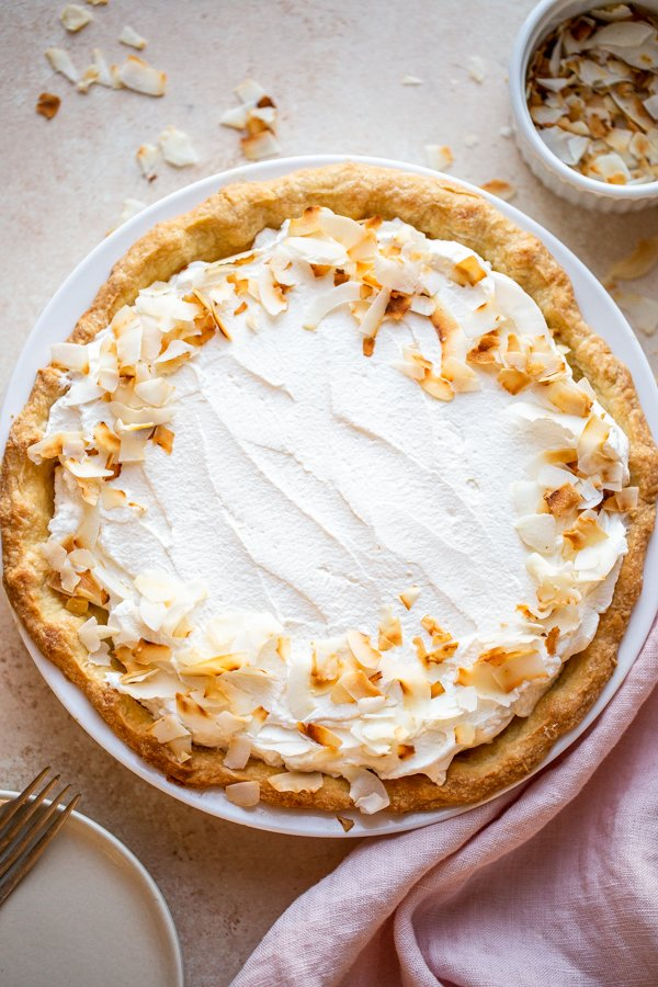 coconut cream pie on a beige counter with toasted coconut and a pink napkin