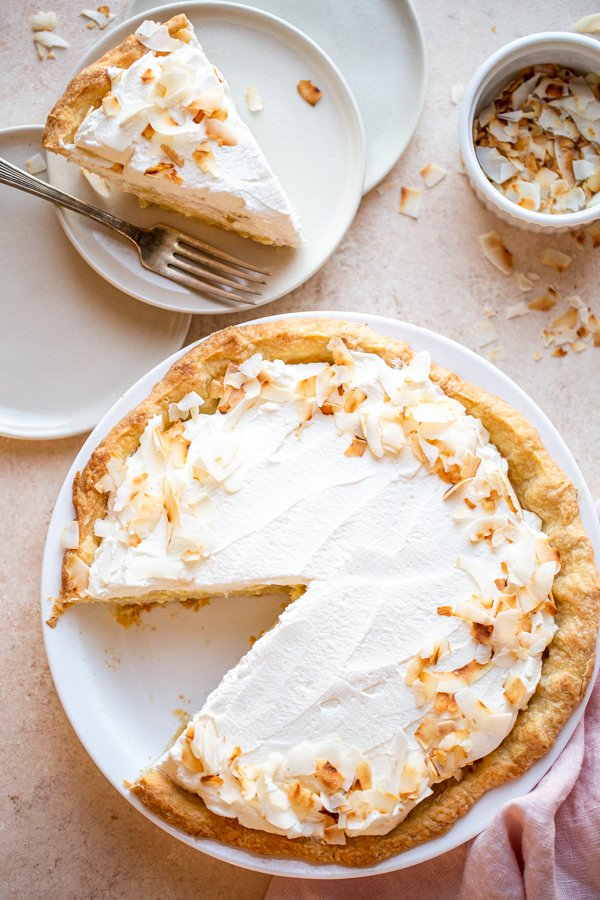 coconut cream pie on a beige counter with toasted coconut and a pink napkin and a slice cut out