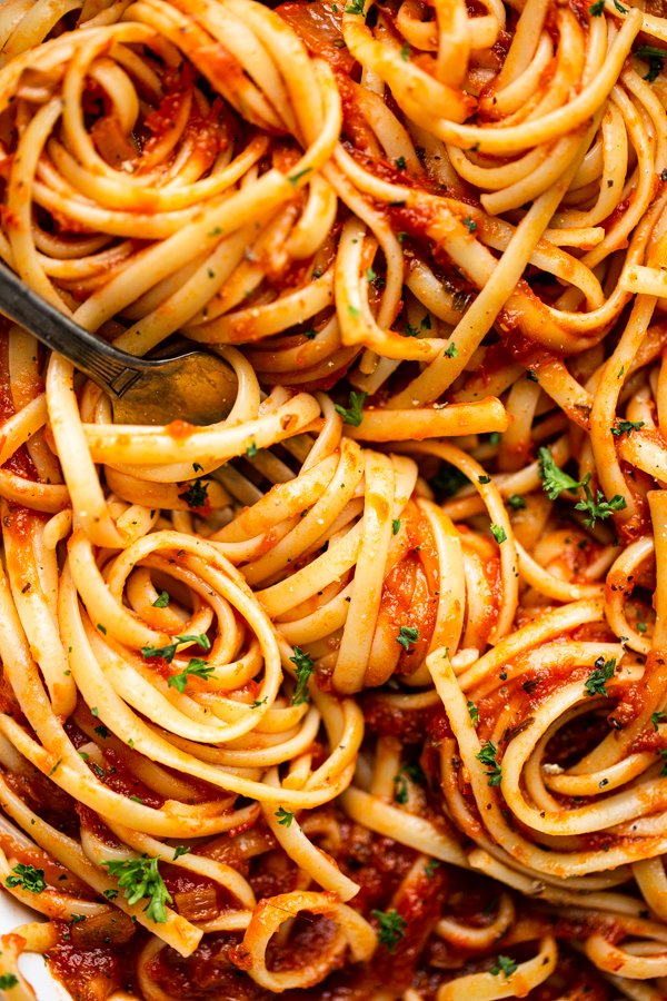 marinara sauce over pasta in a white bowl