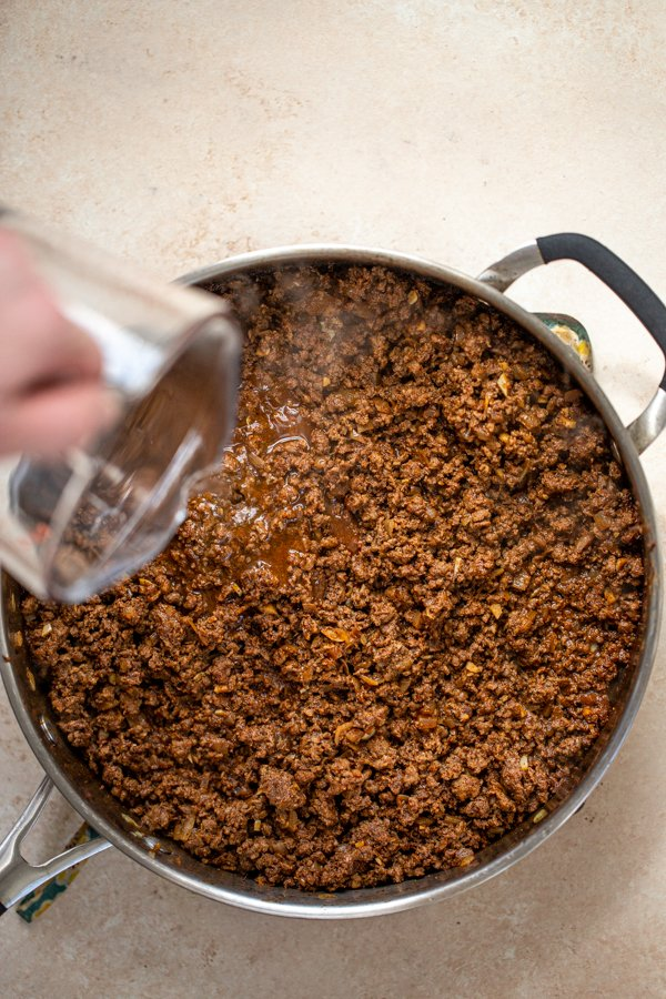 pouring water into taco meat in a pan