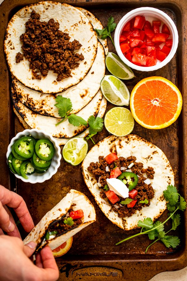 ground venison tacos on a sheet pan with all of the toppings out