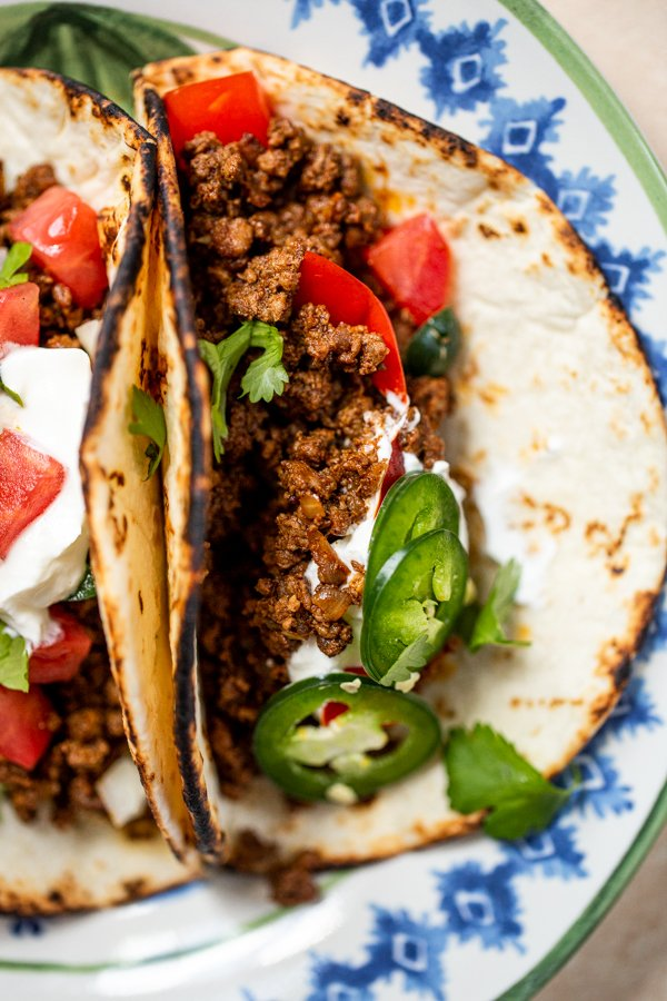 ground venison tacos on a blue and white plate