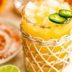 a jalapeno margarita in a rattan glass with a tajin rim