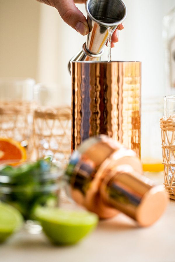 pouring tequila in a copper cocktail shaker