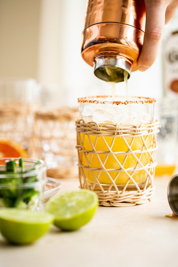 pouring a margarita into a glass with a spicy rim