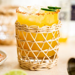 a jalapeno margarita in a rattan glass with a tajin rim