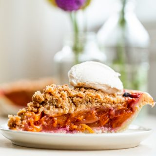Slice of peach pie crumble topped with fresh whipped cream