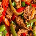 close up on venison cut into strips, sliced onion, red and green peppers sautéed with fajita seasoning topped with cilantro