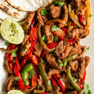 venison sliced in strips with sliced onion & red and green bell peppers, tortillas on the side and halved squeezed limes , topped with cilantro