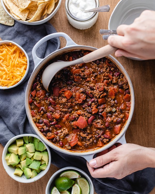 venison chili in a large pot with a ladle on a wood table with toppings spread all around it
