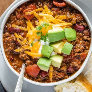 Venison chili, above shot, in a bowl topped with shredded cheddar cheese, chopped avocado and a dollop of sour cream