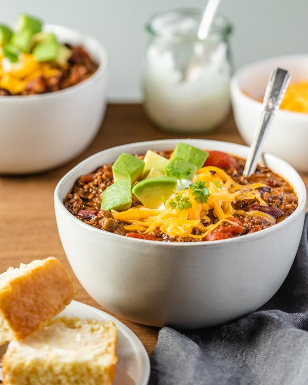 venison chili in a white bowl with cheese and avocado
