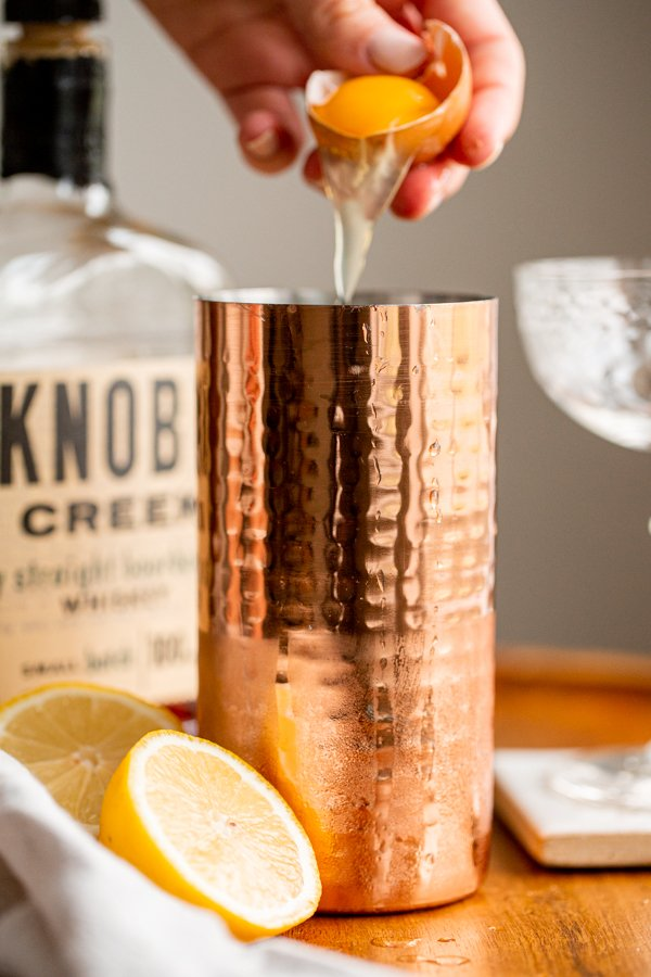 egg white being cracked into a cocktail shaker for a whiskey cocktail