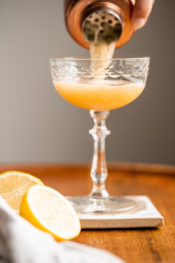 a cocktail shaker pouring a whiskey sour into a coupe glass