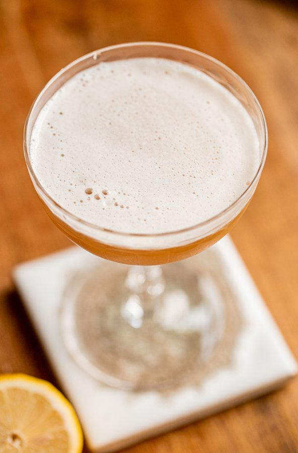 a frothy whiskey sour in a coupe glass